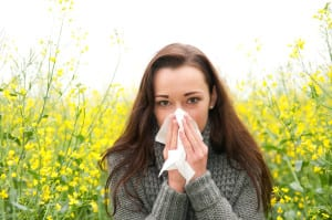 young woman in rape field has hay fever
