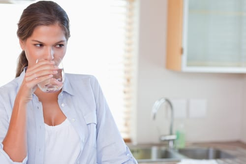 Gorgeous woman drinking a glass of water in her kitchen