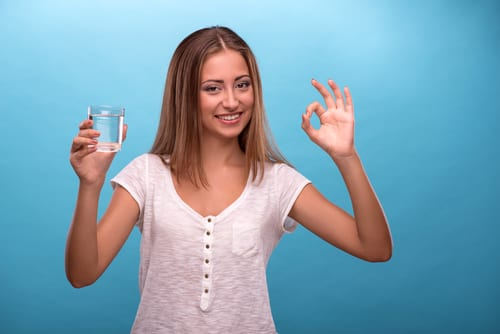Waist-up portrait of young beautiful girl smiling looking at the camera while holding a glass with clean water showing sign OK isolated on blue background with copy place, concept of good quality clean water