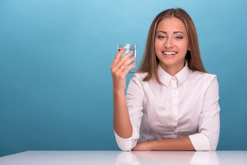 Waist-up portrait of young beautiful girl smiling looking at the camera while sitting at the table holding a glass with clean water in her hand isolated on blue background with copy place