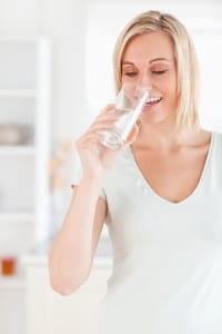 Smiling woman drinking water