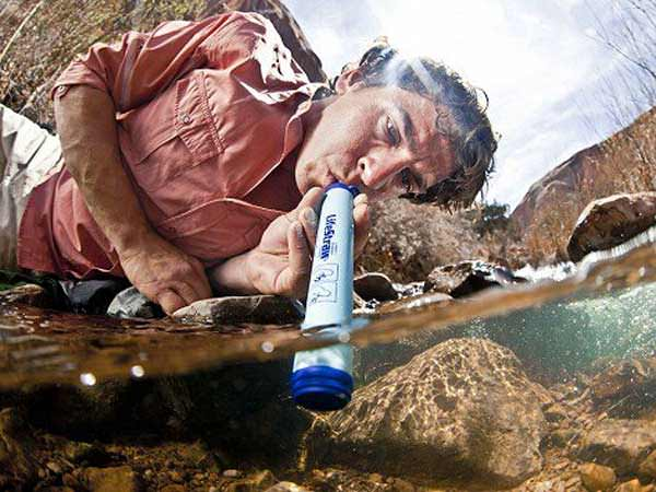 man drinking from survival straw from river